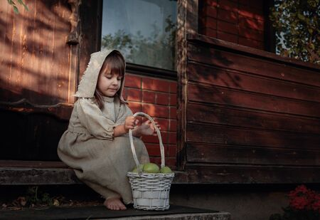 Little barefoot girl in a old canvas dress and a cap on the threshold of the house. Girl with apples on a summer evening near the old house. Standard-Bild - 130023525