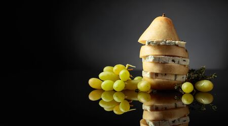 Blue cheese with pear, thyme and grapes on a black reflective background. Copy space. Stok Fotoğraf