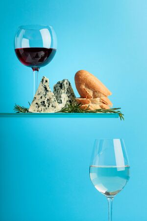 Blue cheese with bread, wine and rosemary on a blue background. Copy space for text. Stok Fotoğraf