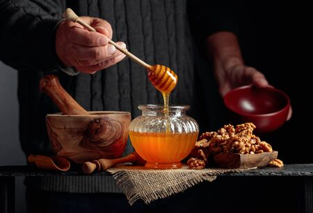 Man in a sweater prepares a breakfast of walnuts and honey. Healthy breakfast background.