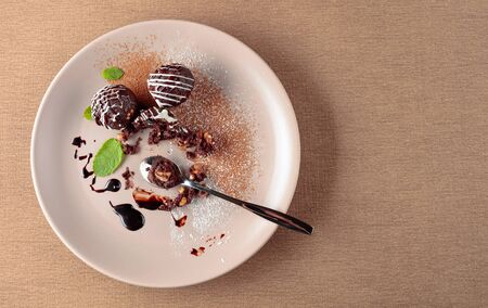 Chocolate balls with mint on a beige plate. Copy space. 스톡 콘텐츠
