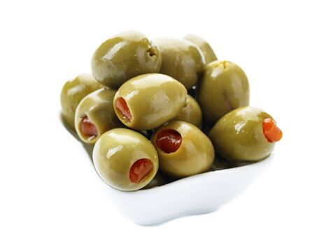 Green olives stuffed with red paprika isolated on white background. 版權商用圖片
