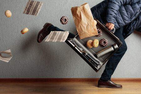 Der Mann rennt ins Büro: Er ist zu spät und verliert den Inhalt seiner Aktentasche. Im Koffer Flakon, Donuts und Servietten.