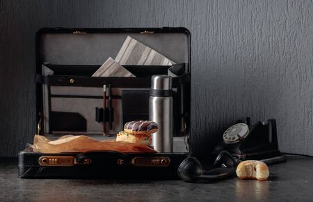 Still life in noir style. Old black phone and unfinished lunch. Donuts and flask in case.