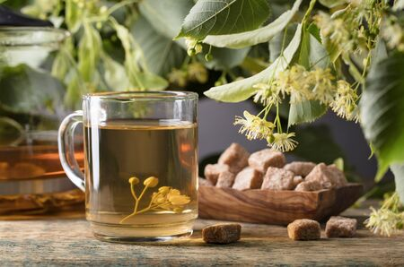 Glass of linden tea with brown sugar and flowers on wooden table. Foto de archivo