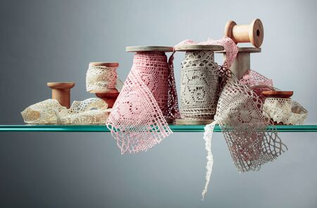 Vintage cotton lace trims on wooden spools. Free space for your text.