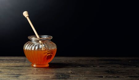 Honey in jar on a old wooden table, black background. Copy space.