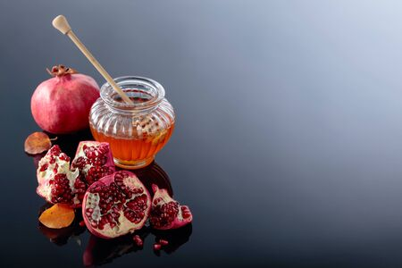 Ripe pomegranate fruits with honey and dried up leaves on a black reflective background.