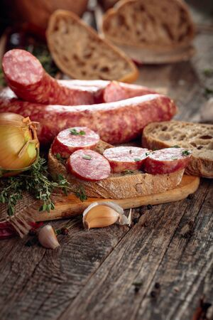 Dry-cured sausage with thyme, onion, garlic and pepper. Sausage with bread and spices on a old wooden table.