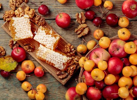 Honey, walnuts and ripe small wild apples. Red and yellow crab apples, healthy organic food. Stock Photo