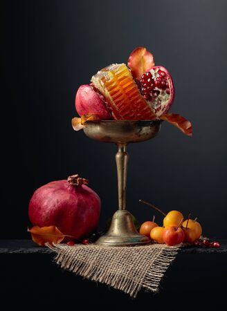 Ripe pomegranate fruits with wild apples and honey. Fruits in old brass vase.
