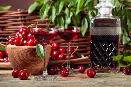 Cherry liquor and red cherries in a wooden bowl on a wooden table in garden. Wicker fence with green leaves in the background. Stock Photo - 131365408