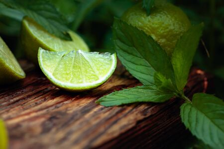 Growing mint in the garden and lime slices. Lime slices and mint leaves on an old wooden background. 스톡 콘텐츠