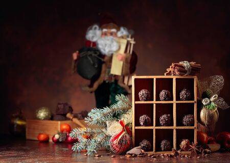 Chocolate candy in wooden box and Christmas decorations. Broken pieces of chocolate, cinnamon sticks, anise and coffee beans on a brown background. Copy space.