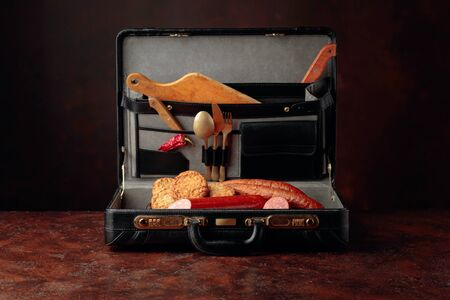 Black leather case with sausage, cutlets and cutlery on brown table. Conceptual image on the theme of food.