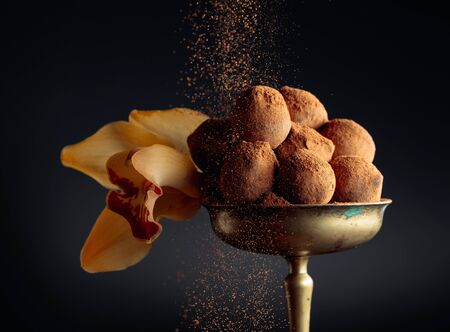 Chocolate truffles in old brass vase sprinkled with cocoa powder and garnished with orchids flower . Copy space.