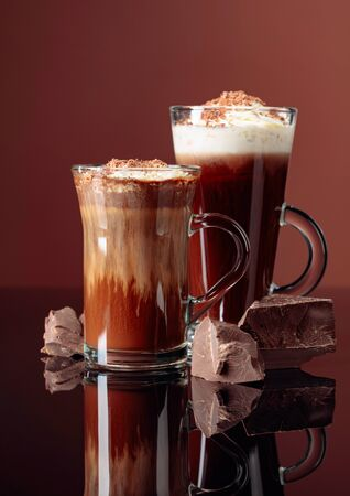 Hot chocolate with whipped cream and pieces of dark chocolate on a brown background. Copy space. 写真素材 - 132108810