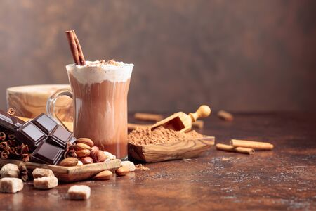 Hot chocolate with cocoa powder, cream, cinnamon, chocolate pieces and other ingredients on a brown background. Copy space for your text.