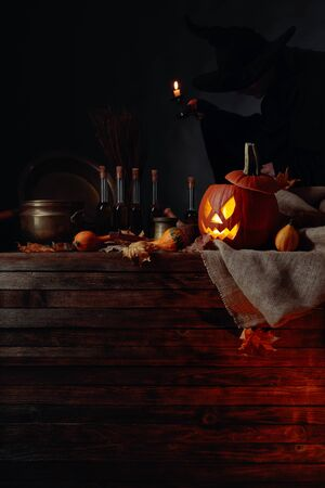 Conceptual image on the theme of Halloween. In the background, a witch in black with a candle in his hand. Stock Photo