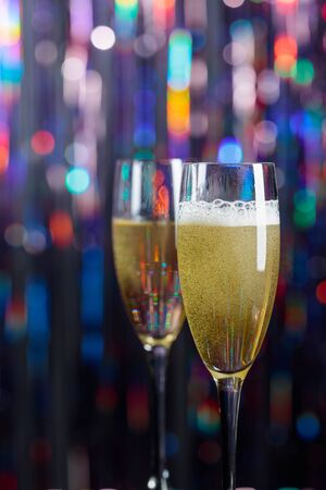 Champagne glasses on lights background. Christmas and New Year holidays background. Copy space.