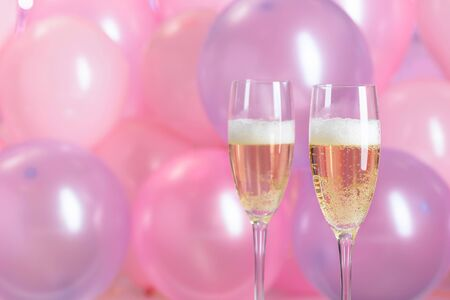 Champagne glasses on pink bubbles background. Christmas and New Year holidays background.  Copy space.