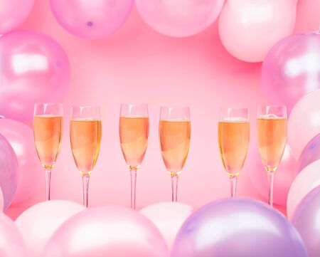 Glasses of champagne on a pink background with pink and purple balloons. Bright background for celebration. Copy space.