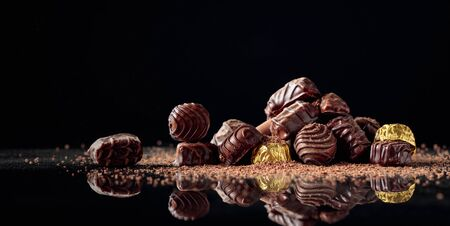 Chocolate candies on a black background sprinkled with chocolate chips. Copy space. Banque d'images