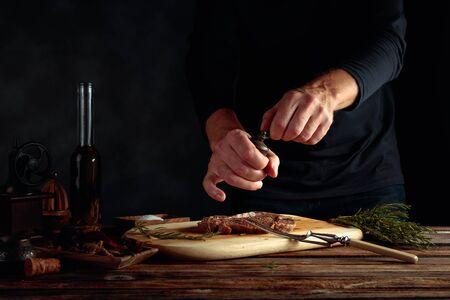 Lo chef prepara la bistecca. Bistecca cruda in salsa con spezie un rosmarino su un vecchio tavolo di legno. Archivio Fotografico