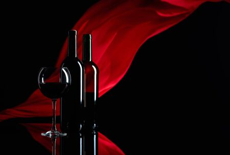 Wineglass and bottles of red wine on a black reflective background. Red satin curtain flutters in the wind. Focus on foreground. Copy space.