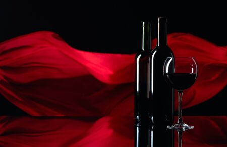 Wineglass and bottles of red wine on a black reflective background. Red satin curtain flutters in the wind. Focus on foreground. Copy space. 版權商用圖片