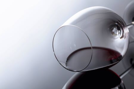 Glass of red wine on a black reflective background. Selective fokus.