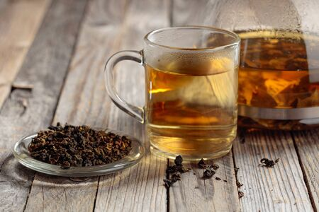 Hot green tea in glass mug. Dried tea leaves and hot drink on a wooden table. Copy space.
