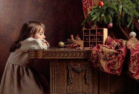 Little girl in an vintage linen dress dreaming near the table with sweets. Chocolates and spices on the table under the Christmas tree. Genre portrait in retro style.