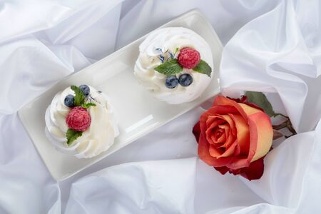 Dessert Pavlova with raspberries, blueberries and mint on a white fabric. Sweet dessert and rose, romantic breakfast. Top view.