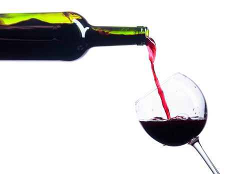 Pouring red wine from bottle to glass isolated on a white background.