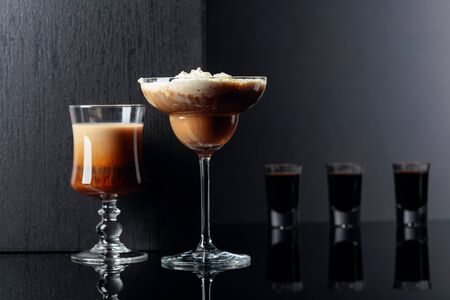 Coffee cocktails and liquor on black reflective background. Copy space for your text.