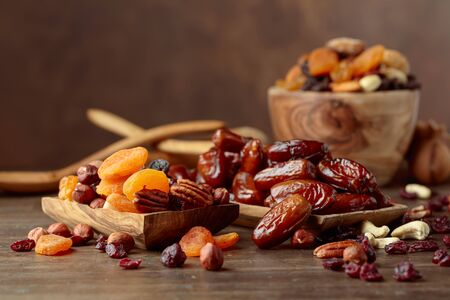 Various dried fruits and nuts on a old wooden table. Standard-Bild - 134910294