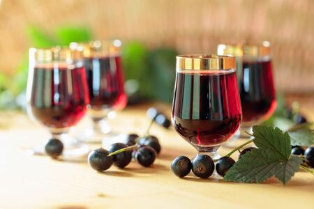 Homemade black currant liqueur and fresh berries, old wooden background.