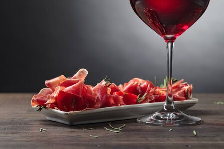 Prosciutto with rosemary and glass of red wine . Copy space.