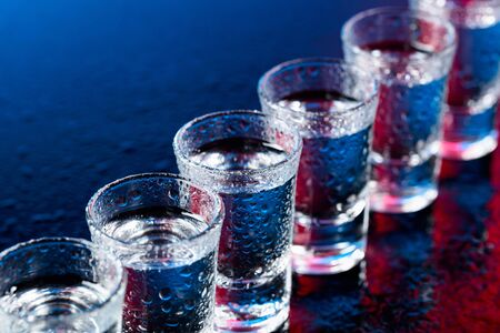 Glasses of vodka on a damp glass table. Selective focus. 版權商用圖片