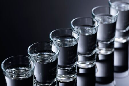 Glasses of vodka on a black reflective background. Selective focus. 版權商用圖片