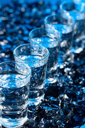 Damp glasses of vodka with ice on a black reflective background. Selective focus.