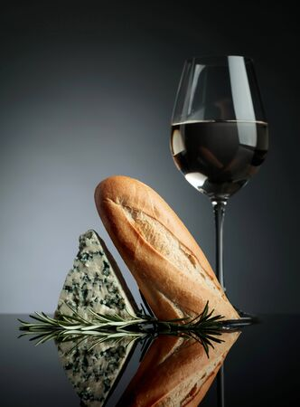 Blue cheese with bread, rosemary and glass of white wine on a black reflective background.