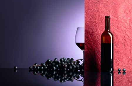 Bottle and glass of red wine on a black table. Free space for your text. Focus on foreground.