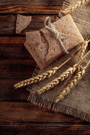 Rye crackers and ears on a old wooden table. Healthy organic food. Top view.
