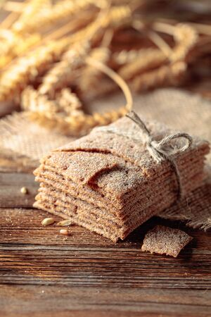 Rye crackers and ears on a old wooden table. Healthy organic food. Stock fotó