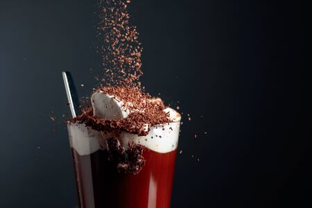 Hot chocolate with marshmallows sprinkled with chocolate crumbs. Black background. Copy space.