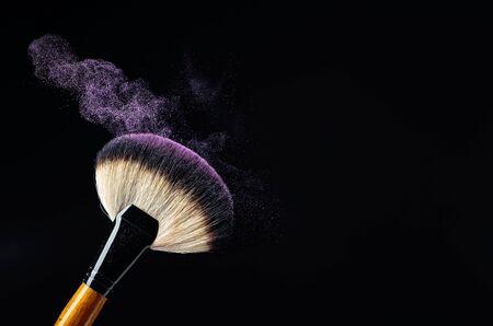 Concepto de maquillaje con un pincel de maquillaje profesional con sombra de ojos púrpura brillante aislado sobre fondo negro. Copie el espacio.