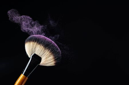 Makeup concept with a professional makeup brush with glowing purple eye shadow isolated on black background. Copy space.