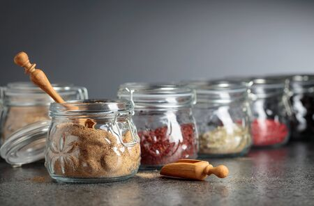 Various spices and herbs in glass jars. Selective focus. Stock Photo